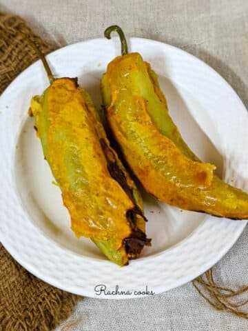 Mirchi bajji on a white plate and a brown mat