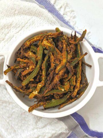 Crispy air fried okra slivers in a white wok