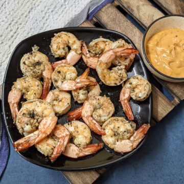 Air fried lemon pepper shrimp on a black plate