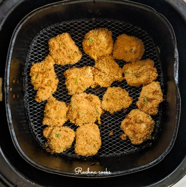 Golden brown chicken nuggets in Air fryer basket after they are done.