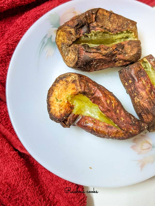 The image shows crispy skin air fryer baked potatoes with centre split and with butter on a white plate.