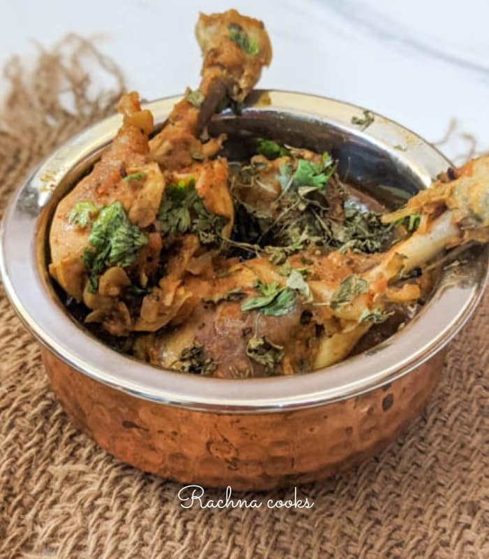 A copper bottomed round pan shows chicken drumsticks coated in rich red curry with a garnish of dry fenugreek and cilantro on white background.