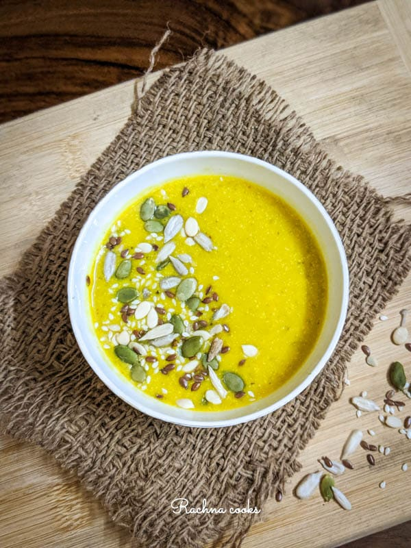 Top shot of yellow pumpkin soup garnished with pumpkin, sesame and melon seeds in a white bowl on a brown mat and light brown background.