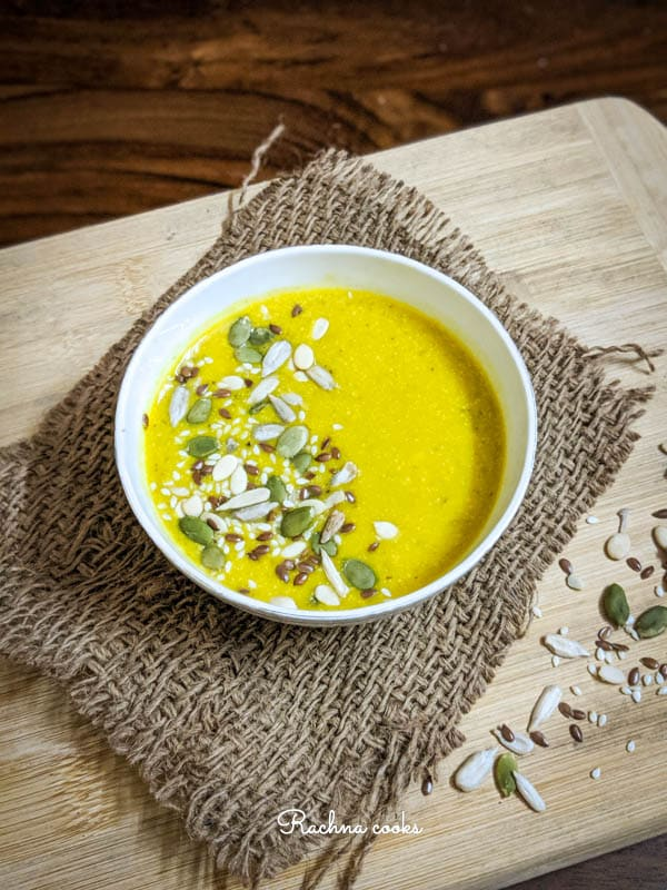 Side shot of yellow pumpkin soup garnished with pumpkin, sesame and melon seeds in a white bowl on a brown mat and light brown background.