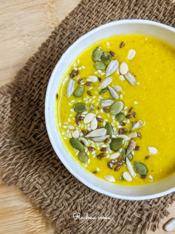 Half Top shot of yellow pumpkin soup garnished with pumpkin, sesame and melon seeds in a white bowl on a brown mat and light brown background.