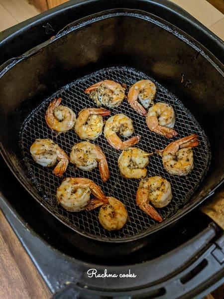 Cooked shrimp on the black Air fryer basket.