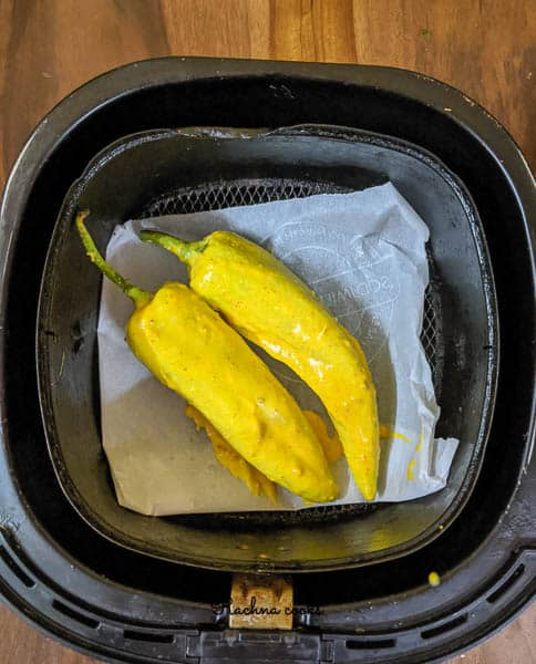 Mirchi bajji with batter on parchment paper in an Air fryer basket.