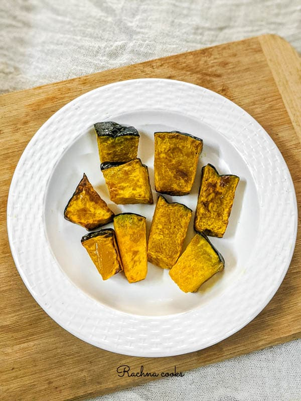 Browned and roasted pumpkin pieces with green skin on a white plate against the background of brown chopping board.
