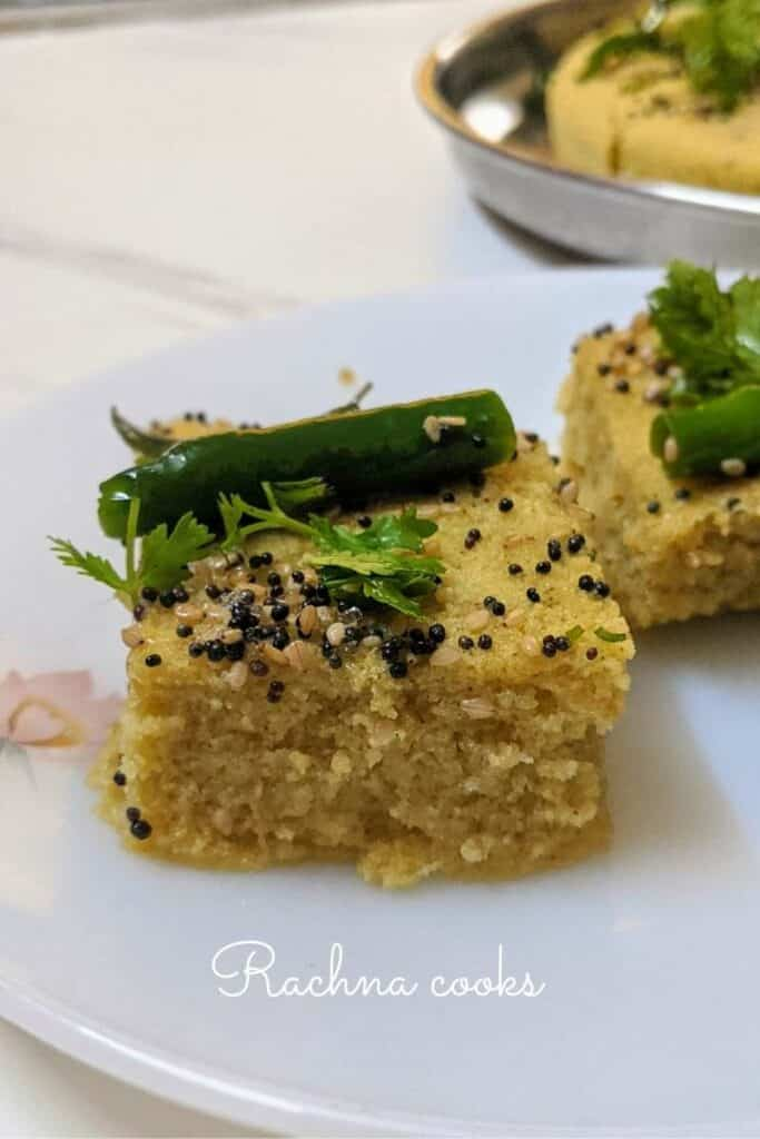 2 pieces of dhokla garnished with mustard seeds, sesame seeds, cilantro and green chillies on a white plate.