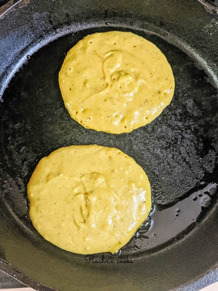 A greased skillet with two pancakes cooking.
