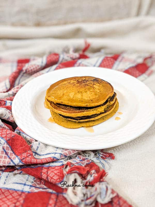 Stacked golden brown pumpkin pancakes with honey drips on a white plate with a red and white checkered napkin in the background.