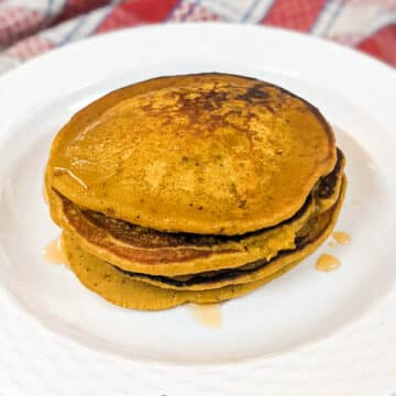 Bright yellow orange pumpkin pancakes that look golden brown with honey on top and stacked together on a white plate with a red and white napkin in background.