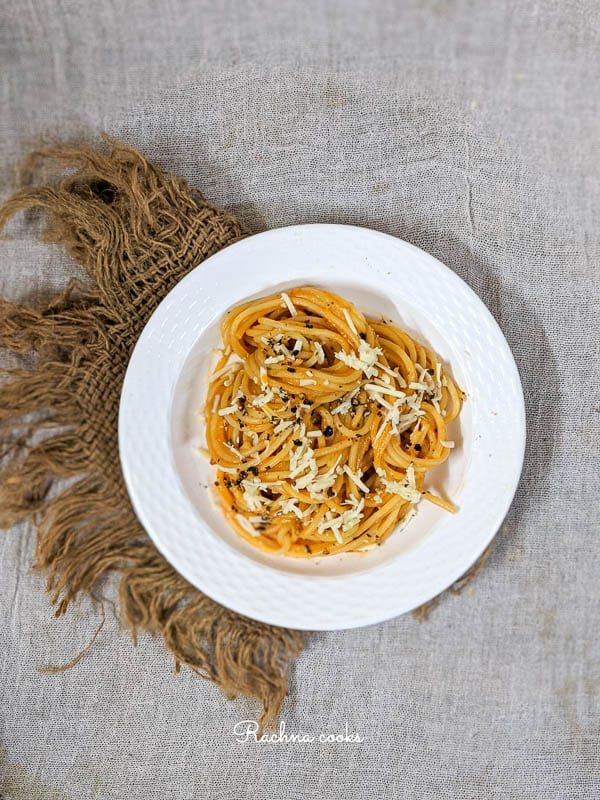 Top shot showing half white plate of pumpkin pasta garnished with cheese and black pepper on a brown mat.