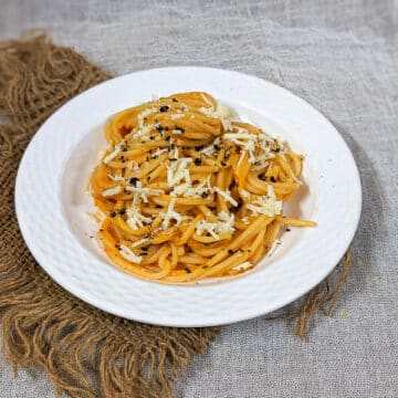 Tasty pumpkin pasta with cheese and pepper garnish on a white plate with a brown mat in the background