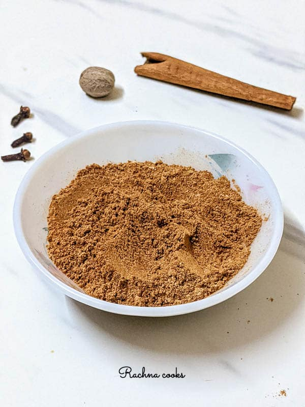 Warm brown pumpkin pie spice in a white bowl with pink flower pattern. Background is white with grey streaks with nutmeg, clove and cinnamon spices.