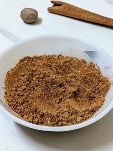 Pumpkin pie spice in a white bowl with a white background and spices in the background.