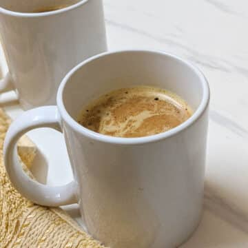 Two white mugs with pumpkin spice latte on a white background with yellow napkin.