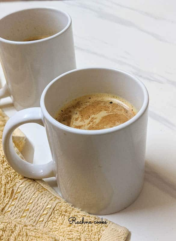 Two white mugs with pumpkin spice latte on a white background with a pale yellow napkin.