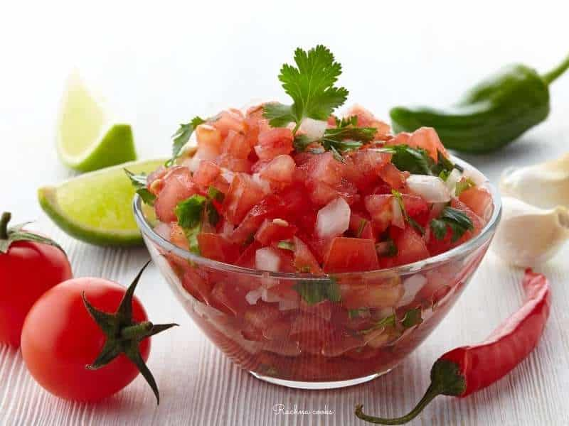 Fresh tomato salsa in a transparent bowl with tomatoes, jalapenos and limes in the background