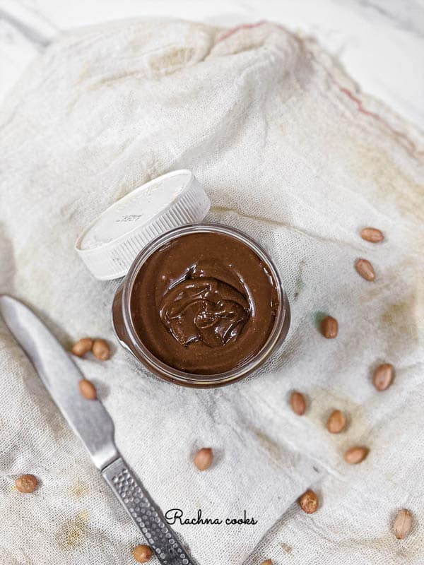 a jar of brown shiny chocolate peanut butter on a white background