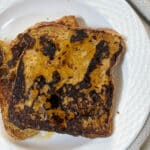 Brown french toast with maple syrup drizzled on top on a white plate