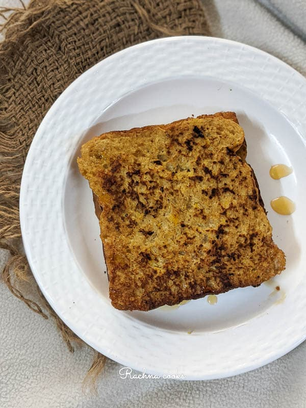 Brown french toast with maple syrup drizzled on top on a white plate on a brown mat.