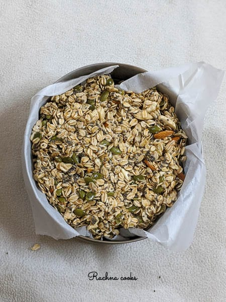 granola mix spread on parchment paper in an oven proof bowl