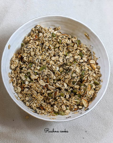 Granola mix in a white bowl ready to be baked.