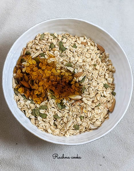 oats with scattered almonds and pepitas have honey and oil poured on them in a white bowl.