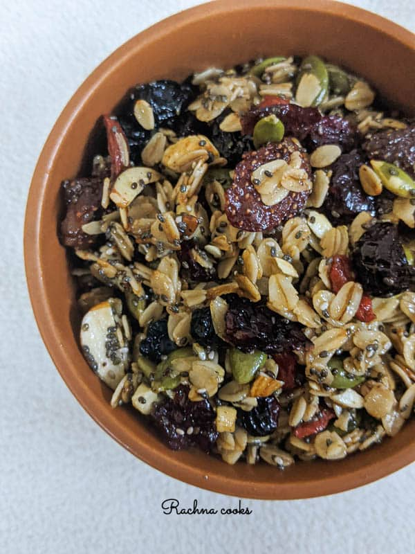 Close up of tasty granola with berries and oats in a brown round bowl on a white background