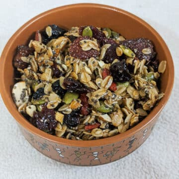 tasty granola with berries and oats in a brown round bowl on a white background