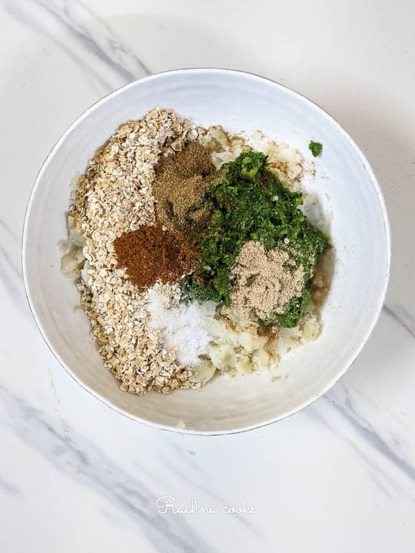 Mashed potato, oats, green mix and spices in a white bowl.