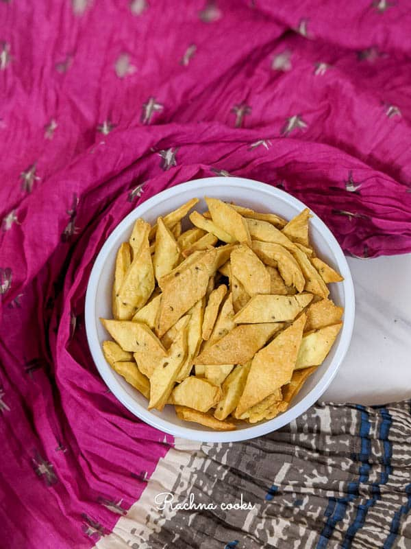 crispy namak pare air fried in a white bowl with a colourful background.