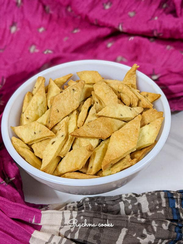 air fryer namak pare in a white bowl with a colourful background.