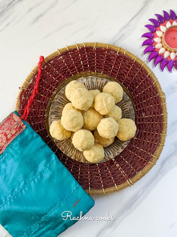 beautiful besan ladoos on a brass plate with an ethnic background.