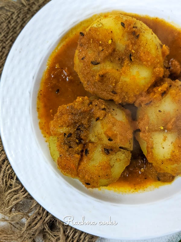 Bharwa tinda or stuffed apple gourd in a curry on a white plate.