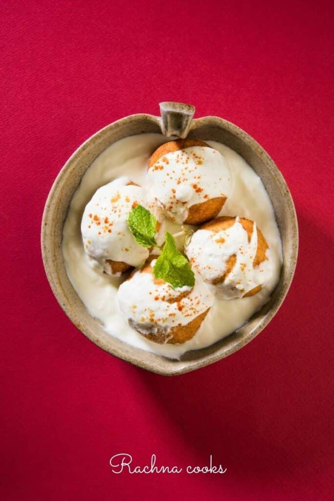 Dahi vadas in a platter with a red background