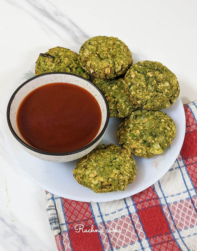 Green kebabs with ketchup on a white plate with a red and white checked napkin.