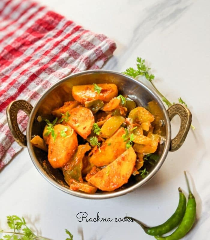 aloo capsicum sabzi in a kadhai with a checked red napkin in the background