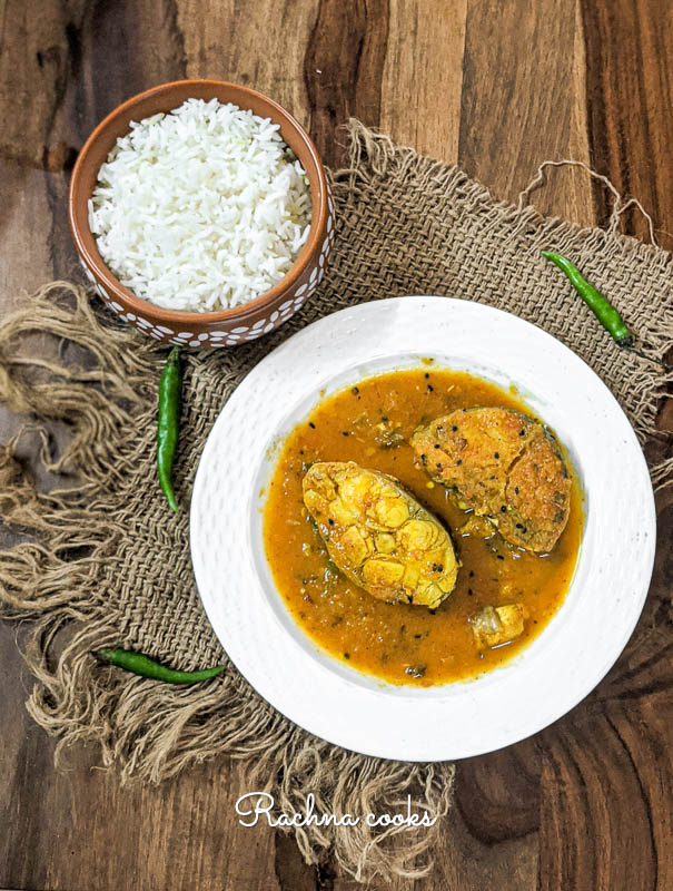 fish fillets in a brown curry in a white plate.