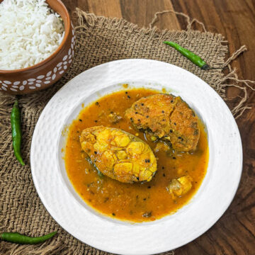 Bengali fish curry with fish fillets in a white plate