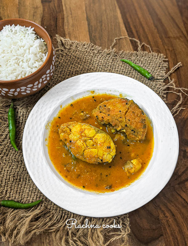 fish fillets in a spicy brown curry in a white plate.