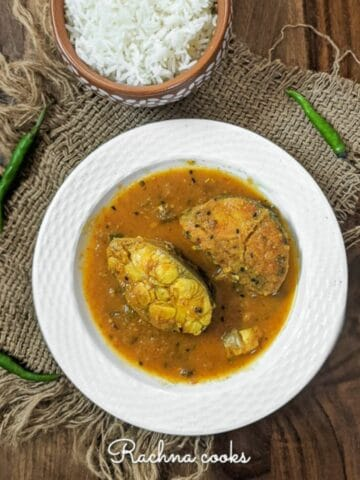 Bengali fish curry in a white plate served with boiled rice