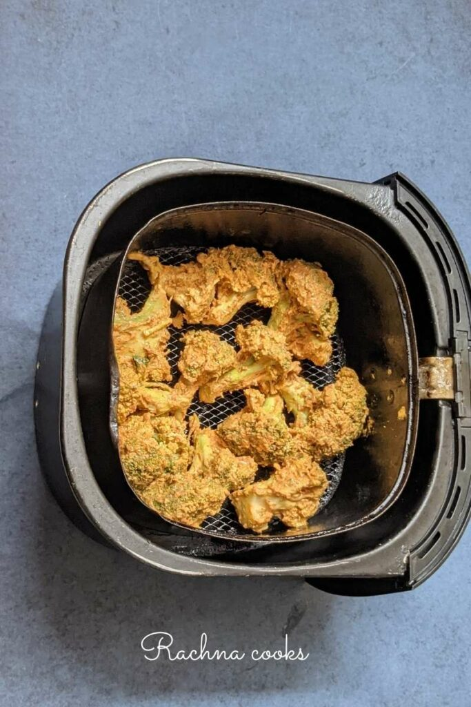 Marinated broccoli in the Air fryer basket.