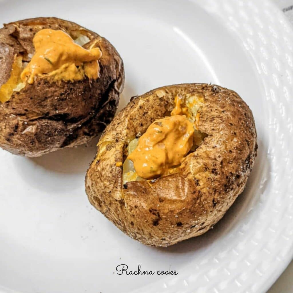 Crispy brown air fryer baked potatoes with a spicy mayo dollop on top on a white background.
