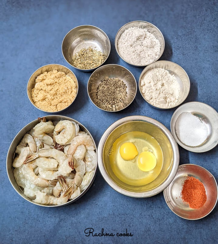 Ingredients to make coconut shrimp -- peeled shrimp, eggs, herbs, breadcrumbs, coconut flakes, flour.