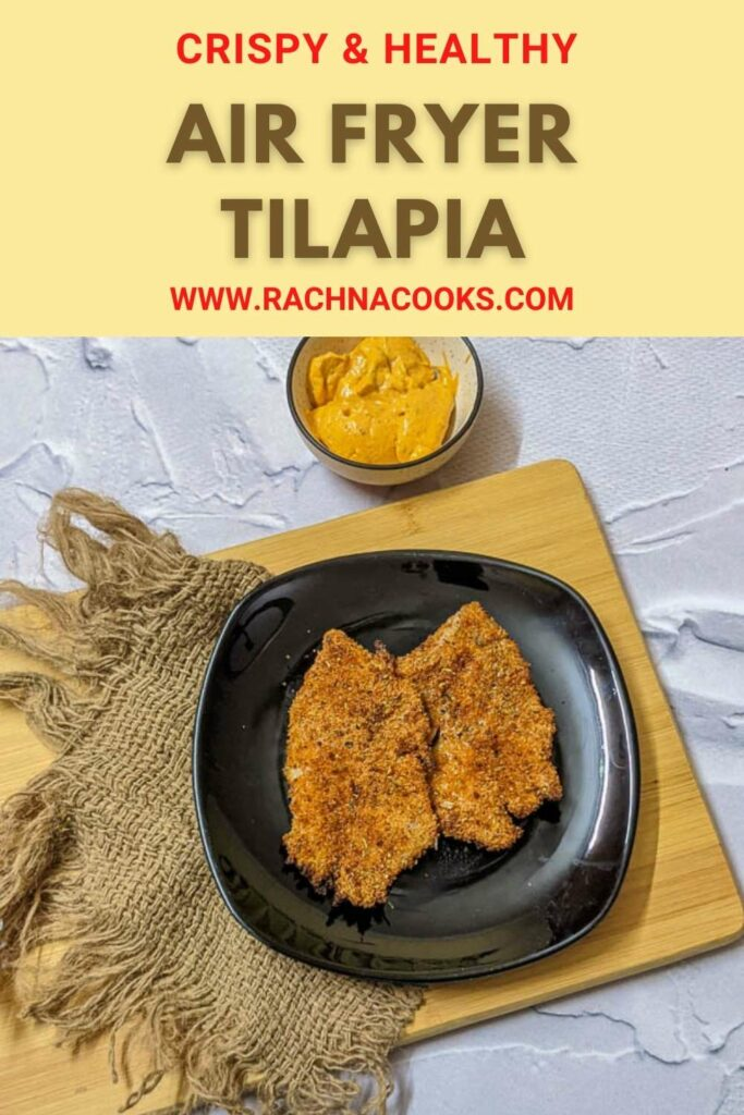Air fried browned tilapia fillets on a black plate with a bowl of dip by the side.