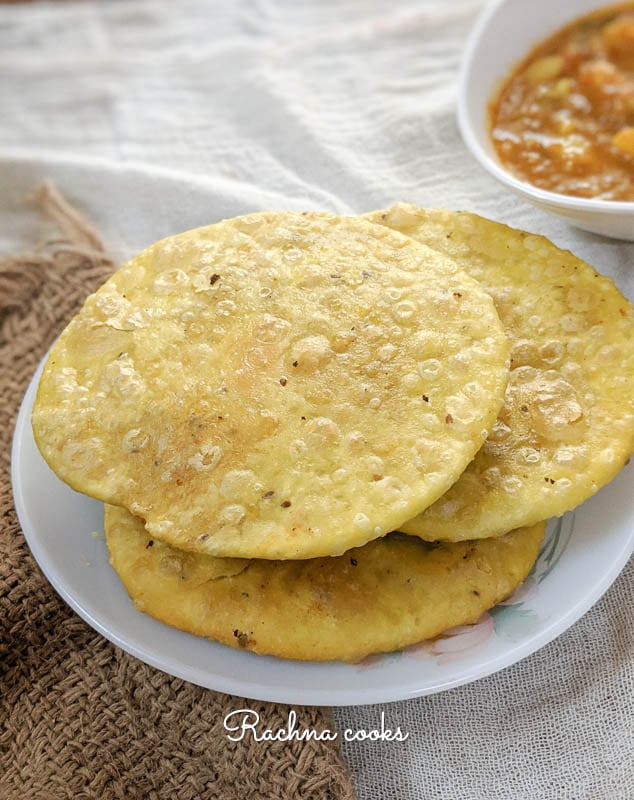 urad dal kachoris on a white plate with tari wale aloo in the background