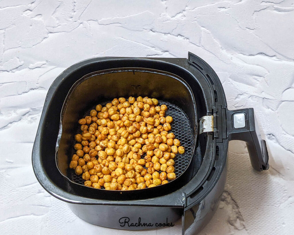 dark chickpeas in air fryer basket after applying spice mix