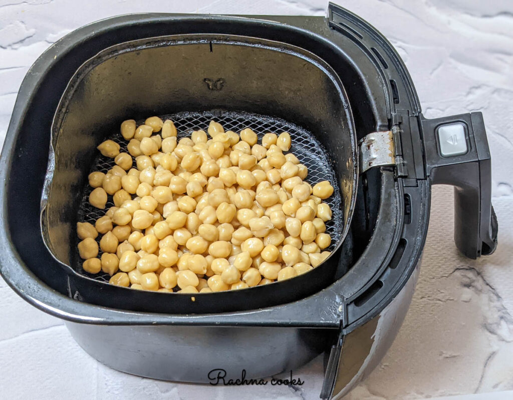 chickpeas spread in air fryer basket for air frying